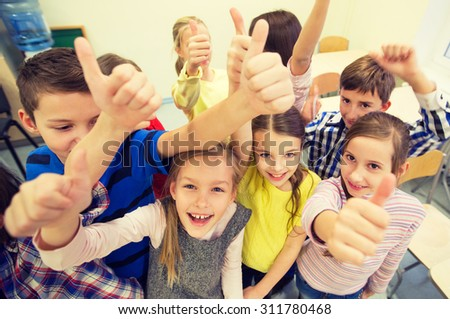 education, elementary school, learning, gesture and people concept - group of school kids and showing thumbs up in classroom - stock photo