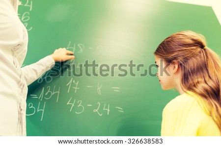 education, elementary school, learning, math and people concept - close up of little schoolgirl with teacher and task on chalk board at classroom