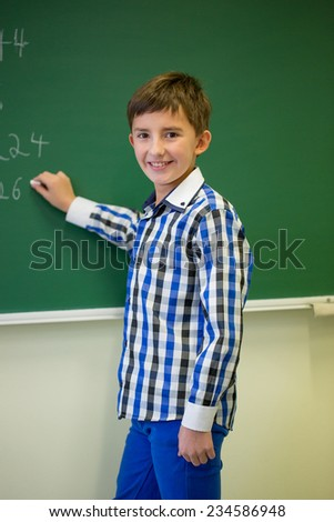 education, elementary school, learning, math and people concept - little smiling schoolboy writing numbers on green chalk board in classroom - stock photo