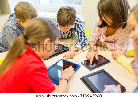 education, elementary school, learning, technology and people concept - group of school kids with tablet pc computer having fun and playing on break in classroom - stock photo