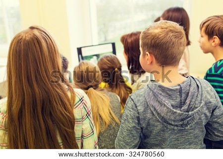 education, elementary school, learning, technology and people concept - group of school kids with teacher looking to computer monitor in classroom from back - stock photo