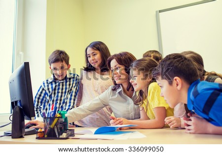 education, elementary school, learning, technology and people concept - group of school kids with teacher looking to computer monitor in classroom - stock photo