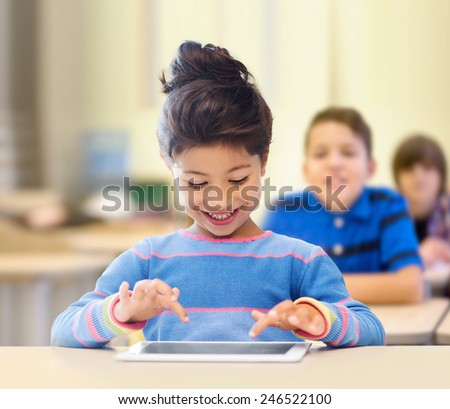 education, elementary school, technology and children concept - happy little student girl with tablet pc over classroom and classmates background - stock photo