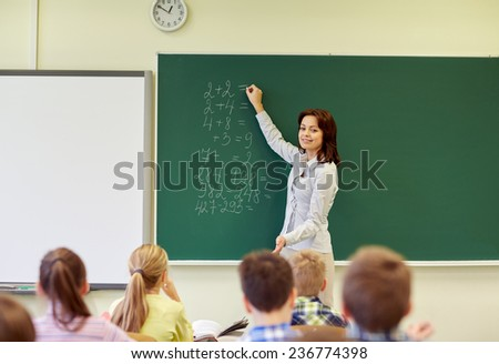education, elementary, teaching, math and people concept - group of school kids and teacher writing mathematic task on green chalkboard in classroom