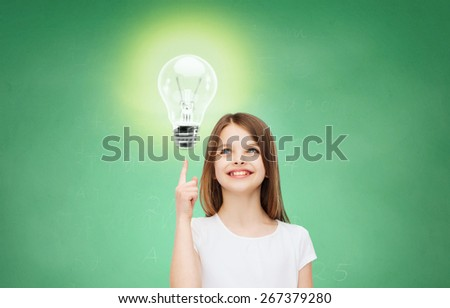 education, energy saving, advertising and people concept - smiling little girl in white blank t-shirt pointing finger up to light bulb over green chalk board background - stock photo