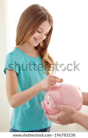 education, family, child and money saving concept - father holding piggy bank and child putting coins into it - stock photo