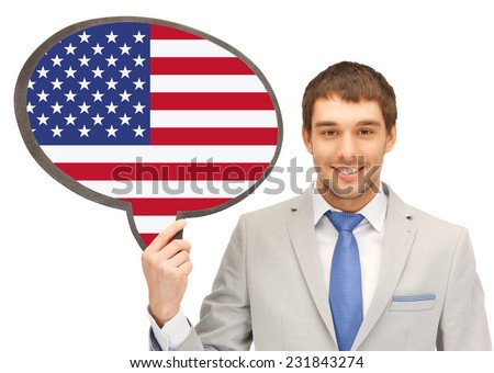 education, foreign language, english, people and communication concept - smiling young man or businessman in tie and suit holding text bubble of american flag - stock photo