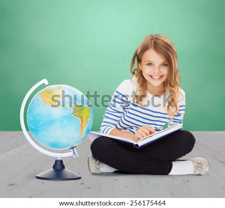 education, geography, childhood, people and school concept - little student girl studying with globe and book over green chalk board background - stock photo