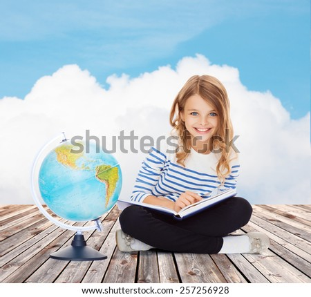 education, geography, childhood, people and school concept - little student girl studying with globe and book over blue sky and cloud background - stock photo