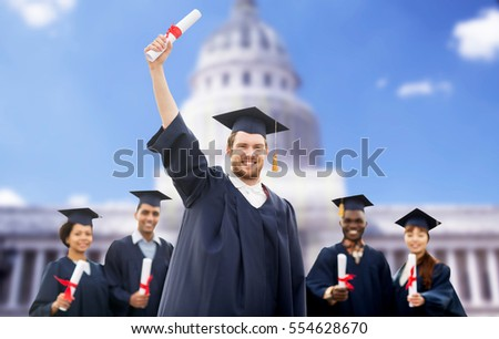 education, graduation and people concept - group of happy international students in mortar boards and bachelor gowns with diplomas over american white house background