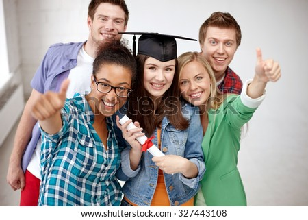education, graduation, gesture and people concept - group of smiling students in mortarboard with diploma showing thumbs up - stock photo