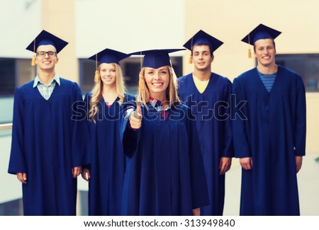 education, graduation, gesture and people concept - group of smiling students in mortarboards and gowns showing thumbs up outdoors - stock photo