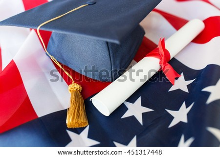 education, graduation, patriotism and nationalism concept - close up of bachelor hat and diploma on american flag - stock photo
