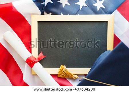 education, graduation, patriotism and nationalism concept - close up of bachelor hat, blackboard and diploma on american flag - stock photo