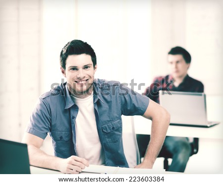 education - group of smiling students with laptops at school - stock photo