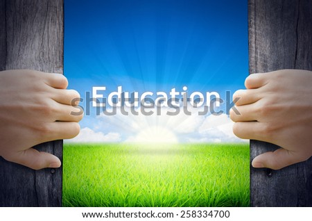 Education. Hand opening an old wooden door and found Education word floating over green field and bright blue Sky Sunrise. - stock photo