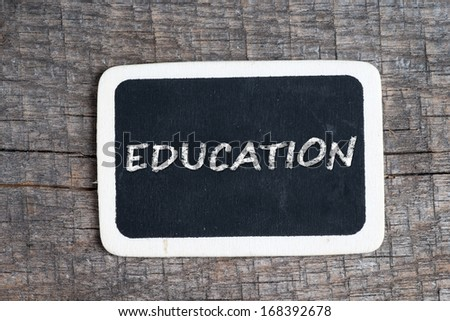 Education handwritten with white chalk on a blackboard on wood background - stock photo