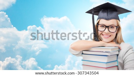 education, high school, knowledge, and people concept - picture of happy student girl or woman in trencher cap with stack of books over blue sky and clouds background - stock photo