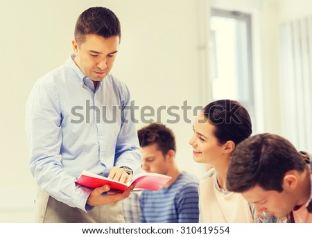 education, high school, teamwork and people concept - group of smiling students and teacher with notebook in classroom - stock photo