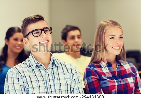education, high school, teamwork and people concept - group of smiling students sitting in lecture hall - stock photo