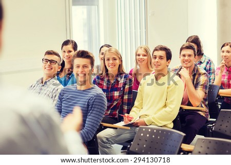 education, high school, teamwork and people concept - group of smiling students with notebooks and teacher in classroom - stock photo
