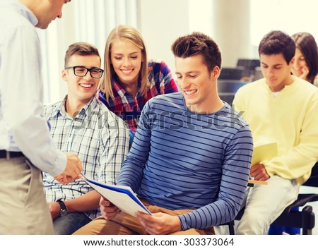 education, high school, teamwork and people concept - group of smiling students with notebooks and teacher talking in classroom - stock photo