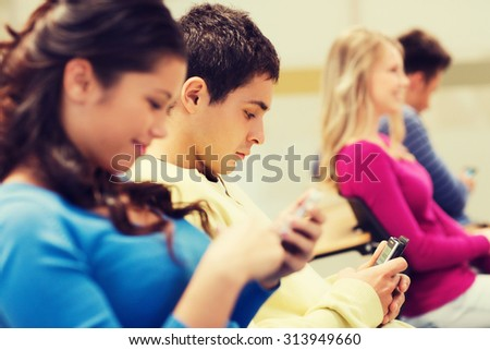 education, high school, teamwork and people concept - group of smiling students with smartphones in lecture hall