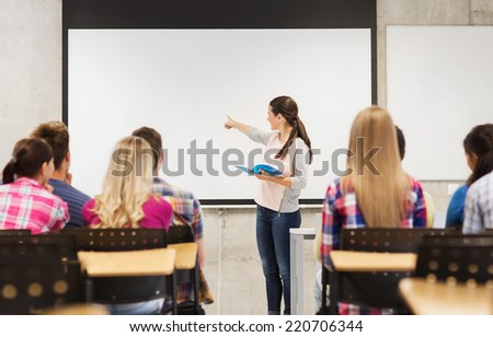 education, high school, teamwork and people concept - smiling student girl with notebook standing and pointing finger in front of students in classroom