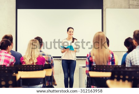 education, high school, teamwork and people concept - smiling student girl with notebook standing in front of students in classroom - stock photo