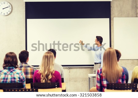 education, high school, teamwork and people concept - smiling teacher standing in front of students and writing something on white board in classroom - stock photo