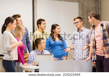 education, high school, technology and people concept - group of smiling students and teacher with laptop computer in classroom