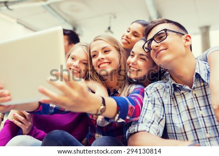 education, high school, technology and people concept - group of smiling students with tablet pc computer taking photo or video indoors - stock photo