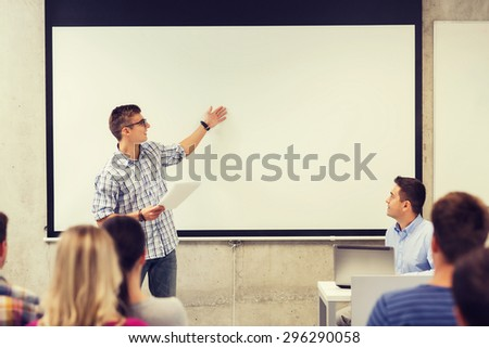 education, high school, technology and people concept - smiling student boy in glasses with notepad, laptop computer standing in front of students and teacher in classroom - stock photo