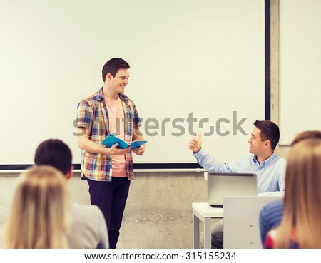 education, high school, technology and people concept - smiling student boy with notebook, laptop computer standing in front of students and teacher showing thumbs up gesture in classroom - stock photo