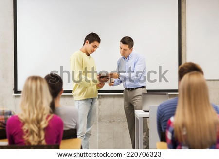 education, high school, technology and people concept - smiling student boy with tablet pc, laptop computer standing in front of students and teacher in classroom