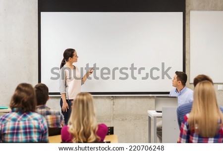 education, high school, technology and people concept - smiling student girl with remote control, laptop computer standing in front of white board and teacher in classroom