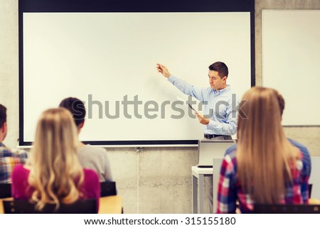 education, high school, technology and people concept - teacher with notepad, laptop computer standing in front of students and showing something on white board in classroom - stock photo