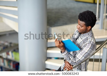 education, high school, university, learning and people concept - happy african american student boy or young man reading book on stairs at library