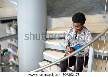 education, high school, university, learning and people concept - happy african american student boy or young man reading book sitting on stairs at library