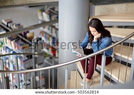 education, high school, university, learning and people concept - student girl reading book sitting on stairs at library