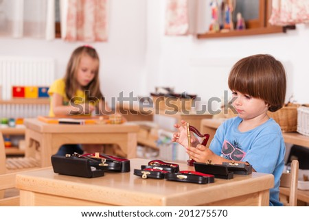 Education image from a kindergarten: child playing his toy harp at his table - stock photo