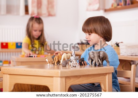 Education image from a kindergarten: child playing with his animal toys at his table