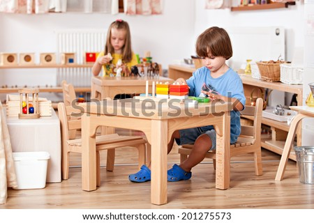 Education image from a kindergarten: child playing with toys at his table