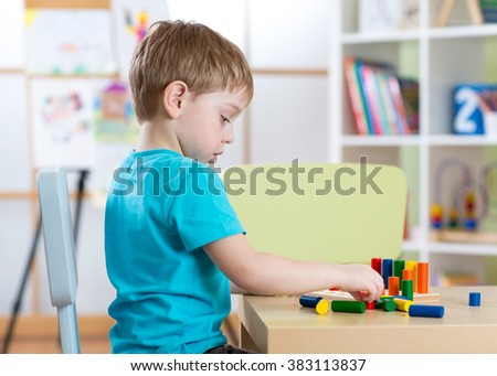 Education image from kindergarten. Child boy playing with toys at table