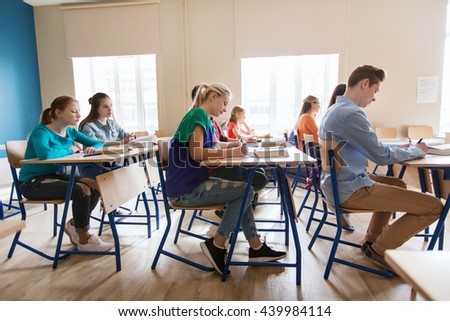 education, learning and people concept - group of students with books writing school test - stock photo