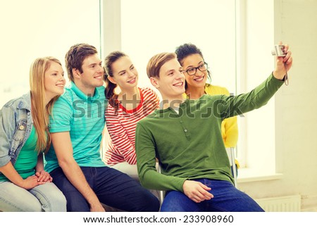 education, leisure and technology concept - five smiling students taking picture with digital camera at school - stock photo
