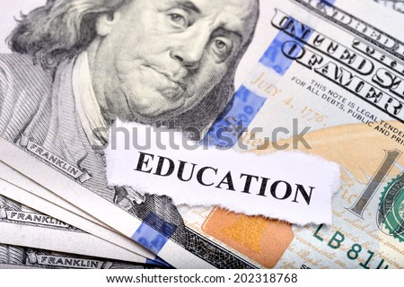 Education loan concept with dollar note and paper on foreground - stock photo