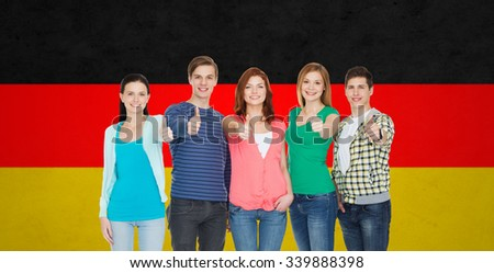 education, nationality, gesture and people concept - group of smiling friends or students standing and showing thumbs up over german flag background - stock photo
