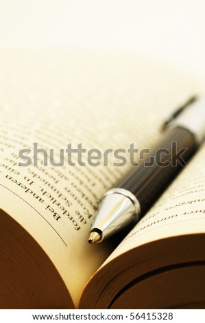 education or reading concept with book and pen - stock photo