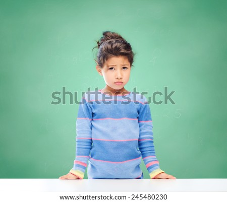 education, people, childhood and emotions concept - sad little school girl over green chalk board background